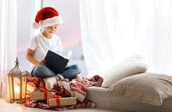 Leuk weinig kind in het verhaal van de lezingskerstmis van de Kerstmanhoed terwijl het zitten op vensterbank royalty-vrije stock fotografie