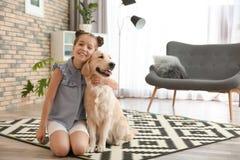 Leuk weinig kind met haar huisdier op vloer stock foto's
