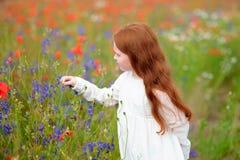 Leuk weinig kindmeisje die met rood hoofd een bloem in openlucht i houden Stock Foto