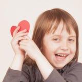 Leuk weinig kindmeisje die rood hart houden als symbool van liefde en amorousness royalty-vrije stock afbeeldingen
