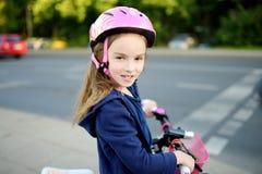 Leuk weinig kleutermeisje die een fiets in een stad berijden royalty-vrije stock afbeelding
