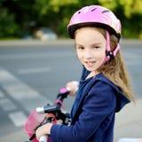 Leuk weinig kleutermeisje die een fiets in een stad berijden stock foto's