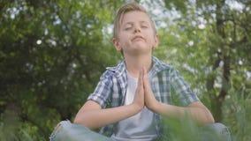 Leuk weinig knappe jongenszitting op gras het mediteren De yoga van kindpraktijken De geestelijke ontwikkeling van jonge geitjes stock video
