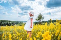 Leuk weinig lachend meisje die op gebied van gele bloemen lopen royalty-vrije stock fotografie
