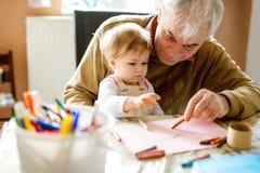 Leuk weinig meisje van de babypeuter en het knappe hogere grootvader schilderen met kleurrijke potloden thuis Kleinkind en mens stock foto's