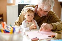Leuk weinig meisje van de babypeuter en het knappe hogere grootvader schilderen met kleurrijke potloden thuis Kleinkind en mens stock afbeeldingen