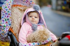 Leuk weinig mooie zitting van het babymeisje in de kinderwagen of de wandelwagen op de herfstdag Gelukkig glimlachend kind in war royalty-vrije stock foto