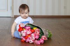 Leuk weinig nadenkende zitting van de babyjongen dichtbij de bos van tulpen royalty-vrije stock afbeeldingen