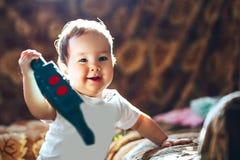 Leuk weinig peutermeisje dat zich dichtbij bed bevindt en met kleurrijke plastic stuk speelgoed Achter Lichte Wijze speelt stof l stock afbeelding