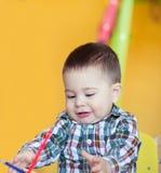 Leuk weinig tekening van de babyjongen met kleurrijke potloden royalty-vrije stock afbeeldingen