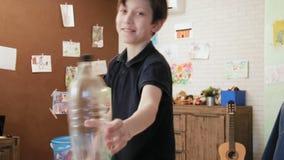 Leuk weinig uitdaging van de de flessentik van het jongens speelwater in zijn ruimte stock video