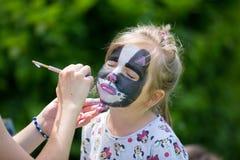 Leuk weinig vijf jaar oud meisjes, die haar die gezicht hebben wordt geschilderd als kitt Royalty-vrije Stock Afbeelding
