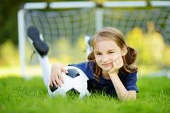 Leuk weinig voetballer die pret hebben die een voetbalspel op zonnige de zomerdag spelen Sportactiviteiten voor kinderen royalty-vrije stock afbeeldingen
