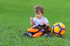 Leuk weinig zitting van de babyjongen met de bal van het oragevoetbal op groene de voetballaarzen van de grasholding in zijn hand royalty-vrije stock foto