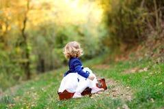 Leuk weinig zitting van het peutermeisje op koffer in de herfstpark Het gelukkige gezonde baby genieten die met ouders lopen zonn royalty-vrije stock fotografie