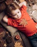 Leuk wordt weinig kindjongen klaar voor de herfst Weinig kindjongen ligt op warme algemene dromen van de warme herfst kid stock fotografie