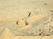 Leuk zandbeeldhouwwerk die een mens vertegenwoordigen die op het strand met neer gezicht leggen Het eiland van Aruba caraïbisch stock afbeeldingen