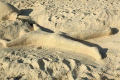 Leuk zandbeeldhouwwerk die een mens vertegenwoordigen die op het strand met neer gezicht leggen Het eiland van Aruba caraïbisch royalty-vrije stock afbeelding