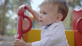 Leuk zit weinig babyjongen met grote ogen op kinderenschommeling in speelplaats in de zomerdag, bekijkend camera stock videobeelden