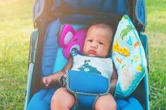 Leuk zit weinig halfjaarlijkse oude Aziatische babyjongen op wandelwagen carriag stock foto's