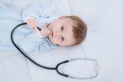 Leuk zuigelingskind die met stethoscoop op de laag liggen stock afbeeldingen