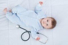 Leuk zuigelingskind die met stethoscoop op de laag liggen stock foto