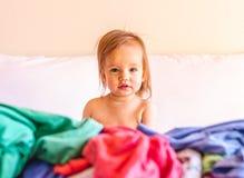Leuke, Aanbiddelijke, Glimlachende, Kaukasische Babyzitting in een Stapel van Vuile Wasserij op Bed stock afbeeldingen