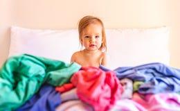 Leuke, Aanbiddelijke, Glimlachende, Kaukasische Babyzitting in een Stapel van Vuile Wasserij op Bed stock afbeelding