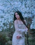 Leuke aantrekkelijke dame met donker lang haar en groene ogen, die zich dichtbij bloeiende magnolia's bevinden, die een verrukkel stock fotografie