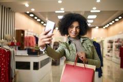 Leuke Afrikaanse Amerikaanse vrouw die selfie met het winkelen zakken en het glimlachen dichtbij kledingsopslag nemen Het zwarte  Stock Foto's