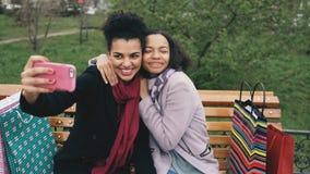 Leuke Afrikaanse Amerikaanse vrouw twee die selfie op smartphone met het winkelen zakken nemen en het glimlachen Meisjes die zitt Stock Afbeeldingen