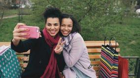 Leuke Afrikaanse Amerikaanse vrouw twee die selfie op smartphone met het winkelen zakken nemen en het glimlachen Meisjes die zitt Royalty-vrije Stock Afbeeldingen