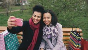 Leuke Afrikaanse Amerikaanse vrouw twee die selfie op smartphone met het winkelen zakken nemen en het glimlachen Meisjes die zitt Royalty-vrije Stock Fotografie