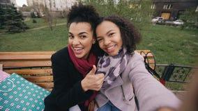 Leuke Afrikaanse Amerikaanse vrouw twee die selfie op smartphone met het winkelen zakken nemen en het glimlachen Meisjes die zitt Royalty-vrije Stock Foto's