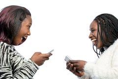 Leuke Afrikaanse tienermeisjes die met slimme telefoons lachen Royalty-vrije Stock Afbeelding