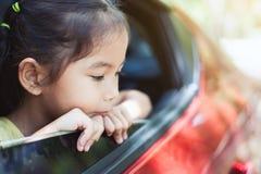 Leuke Aziaat weinig kindmeisje die door auto reizen stock afbeelding