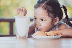 Leuke Aziaat weinig kindmeisje die koekje met melk eten stock afbeeldingen