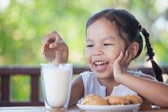 Leuke Aziaat weinig kindmeisje die koekje met melk eten royalty-vrije stock afbeeldingen