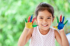 Leuke Aziaat weinig kindmeisje die met geschilderde handen met pret glimlachen Royalty-vrije Stock Fotografie