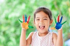 Leuke Aziaat weinig kindmeisje die met geschilderde handen met pret glimlachen Royalty-vrije Stock Foto's