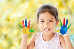 Leuke Aziaat weinig kindmeisje die met geschilderde handen met pret glimlachen Stock Afbeelding