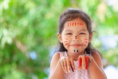 Leuke Aziaat weinig kindmeisje die met geschilderde handen met pret glimlachen Stock Foto