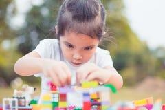 Leuke Aziaat weinig kindmeisje die met kleurrijke blokken spelen Stock Foto's