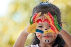 Leuke Aziaat weinig kindmeisje met geschilderde handen maakt hartvorm Royalty-vrije Stock Foto