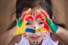 Leuke Aziaat weinig kindmeisje met geschilderde handen maakt hartvorm Stock Afbeelding
