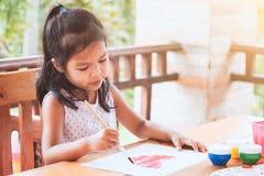 Leuke Aziaat weinig tekening van het kindmeisje en geschilderd een hart royalty-vrije stock afbeelding