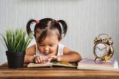 Leuke Aziatische peuter die een boek met wekker lezen stock afbeelding