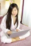Leuke Aziatische vrouw die thuis met computer werken royalty-vrije stock foto's