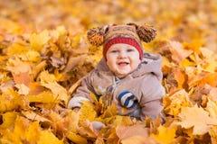 Leuke baby in de herfstbladeren Stock Fotografie