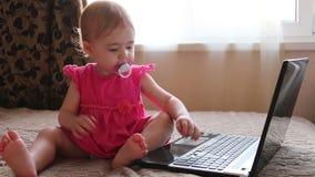Leuke baby die aan computer werkt stock videobeelden